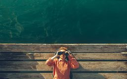 Free Young Beautiful Girl Lies On A Pier Near The Sea And Looks Through Binoculars On The Sky. Travel Search Journey Concept Stock Photography - 110915922