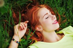 Young beautiful girl in a light green t-shirt lies with clo. Young very beautiful girl in a light green t-shirt lies with closed eyes and smiles happily among Stock Image