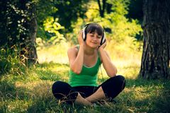 Young beautiful girl listen to music in a park royalty free stock images