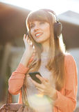 Young beautiful girl listening to MP3 player Royalty Free Stock Images