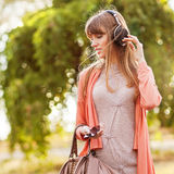 Young beautiful girl listening to MP3 player Royalty Free Stock Photography