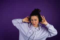 Young beautiful girl listening to music wearing headphones in a sweatshirt on a purple background.  Royalty Free Stock Photography
