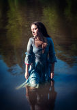 Young beautiful girl in long blue dress standing in the river Royalty Free Stock Photography