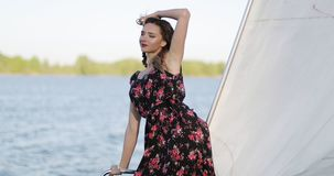 A young beautiful girl in a long bright dress is traveling on a yacht. The model stands near the white sail and looks at the camera. 4K footage stock video footage