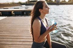 Young beautiful girl with long brown hair in a sports top sits on the wooden pier and holds a bottle of water . royalty free stock photos