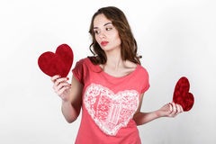 Young beautiful girl with long dark wavy hair. In a pink shirt holding  red heart near her body, the symbol of Valentine's Day Stock Images