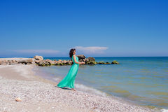 Young beautiful girl in a long dress on the beach in summer Stock Image