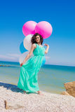 Young beautiful girl in a long dress on the beach in summer Stock Photography