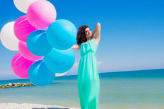 Young beautiful girl in a long dress on the beach in summer Stock Images