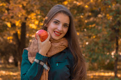 Young beautiful girl with long hair in a dark shirt and  warm scarf keeps Apple looks forward  smiles Stock Photography