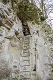 Young beautiful girl with long hair in a down jacket, climbed to the highest ladder in the cave in the rock Stock Photos