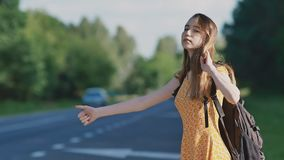 Young beautiful girl with long hair in a dress and a backpack on her back is catching a car on the freeway. She shows a. Sign with her hand. The Sun Summer stock video