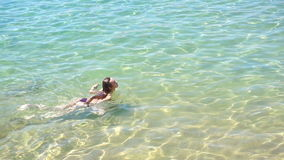 Young beautiful girl with long hair floating in pure transparent sea stock video