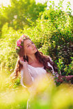Young beautiful girl with long hair in floral wreath in the spring Stock Images