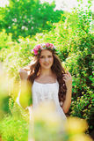 Young beautiful girl with long hair in floral wreath in the spring Royalty Free Stock Photography