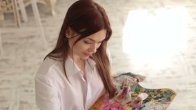 Portrait of a talented girl artist in the studio. Young beautiful girl with long hair is holding a palette with paints and draws a picture on canvas, close-up stock video footage