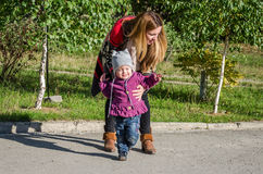 Young beautiful girl with long hair in a jacket mother teaches his daughter to walk their baby's first steps outdoors on a sunny d Royalty Free Stock Image
