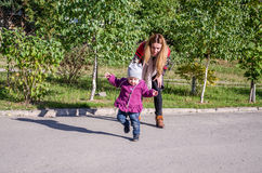 Young beautiful girl with long hair in a jacket mother teaches his daughter to walk their baby's first steps outdoors on a sunny d Royalty Free Stock Images