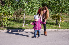 Young beautiful girl with long hair in a jacket mother teaches his daughter to walk their baby's first steps outdoors on a sunny d Stock Image