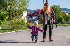 Young beautiful girl with long hair in a jacket mother teaches his daughter to walk their baby's first steps outdoors on a sunny d Stock Photos