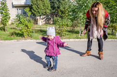 Young beautiful girl with long hair in a jacket mother teaches his daughter to walk their baby's first steps outdoors on a sunny d Stock Photo