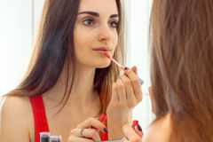 Young beautiful girl with long hair looks in the mirror and paint lips Stock Photography