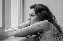 Young beautiful girl with long hair looks out the window stock photography