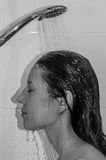 Young beautiful girl with long hair, naked, taking a shower and washing her head Royalty Free Stock Photo
