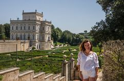 Young beautiful girl with long hair in a park at the villa Pamphili posed by a labyrinth of flowers and plants.  Royalty Free Stock Photography
