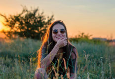 Beautiful young girl laughing in round sunglasses in the sunset light. Young beautiful girl with long hair smiles in round sunglasses in the evening light royalty free stock photo