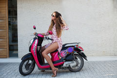 The young beautiful girl with long hair in sunglasses in the pink shirt and brown footwear posing on the scooter develops the fash Stock Image