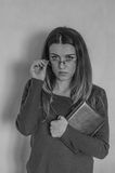 Young beautiful girl with long hair teacher with glasses with a book in his hands after the lecture Royalty Free Stock Photo