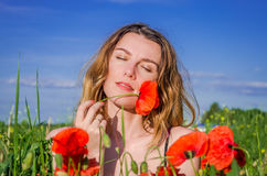 Young beautiful girl with long hair during a walk on a hot summer sunny day over a poppy field enjoying the aroma of a poppy flowe Stock Photos