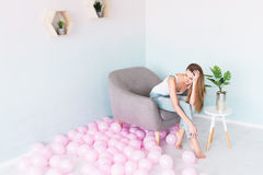 Young beautiful girl with long hair in white singlet and blue jeans with holes sitting in an armchair. Near a lot of pink balloons Royalty Free Stock Photos