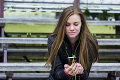 Young beautiful girl look and listening music on your mobile phone on the old stadiums bench. Royalty Free Stock Photos