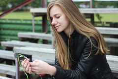 Young beautiful girl look and listening music on your mobile phone on the old stadiums bench. Royalty Free Stock Photo
