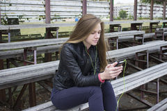 Young beautiful girl look and listening music on your mobile phone on the old stadiums bench. Royalty Free Stock Photography
