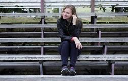 Young beautiful girl look and listening music on your mobile phone the old stadiums bench Royalty Free Stock Image