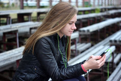 Young beautiful girl look and listening music on your mobile phone  the old stadiums bench Stock Images