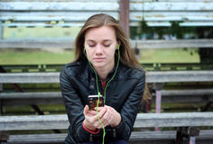 Young beautiful girl look and listening music on your mobile phone  the old stadiums bench Royalty Free Stock Images