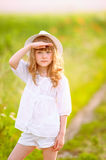 Young beautiful girl looks peacefully off into the distance with. Her hand shielding the sunlight stock photography
