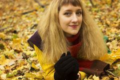Young beautiful girl lying on autumn leaves. Stock Photo