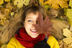 Young beautiful girl lying on autumn leaves and smiling. Stock Photo