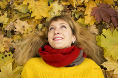 Young beautiful girl lying on autumn leaves and smiling. Royalty Free Stock Photography