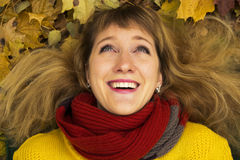 Young beautiful girl lying on autumn leaves and smiling. Royalty Free Stock Images