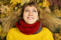 Young beautiful girl lying on autumn leaves and smiling. Stock Photos
