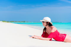 Young beautiful girl lying on the beach at shallow tropical water Royalty Free Stock Images