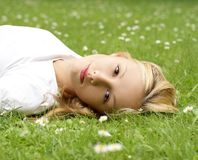 A young and beautiful girl is lying on the grass Stock Photography