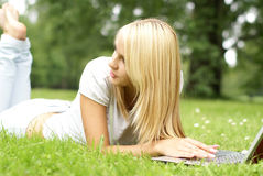 A young and beautiful girl is lying on the grass Stock Images