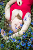 Young beautiful girl lying on grass and flowers with closed eyes Stock Images